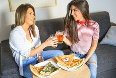 Young women having a lunch together toasting beers and eating pizza - Happy friends enjoying a dinner sitting stock photography