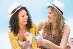 Young women having martini near pool Stock Image