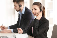 Young woman with headset working. Young women with headset working in office Royalty Free Stock Images