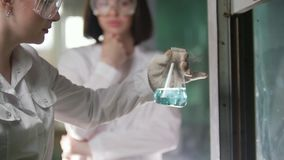 A young women heat of the flasks in medical laboratory stock video footage