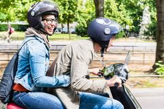 Woman sitting on pillion seat of Vespa. Young women with helmet sitting on pillion seat of Vespa in streets of Berlin Stock Photo