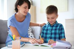 Young woman helping her child with homework. Young women helping her child with homework at home. Elementary school stock image