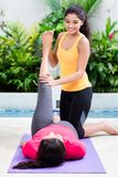 Woman helping her friend to raise leg in abdominal workout Stock Photos