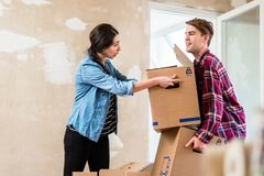 Young woman helping her partner to carry two boxes while moving in royalty free stock image
