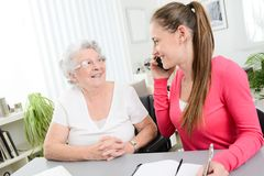 Young woman helping an old senior woman doing paperwork and administrative procedures with laptop computer at home. Young women helping an old senior women doing royalty free stock photography