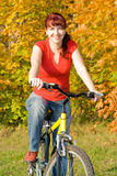 Young woman on her bicycle. Young beautiful happy women on her bicycle in the fall Royalty Free Stock Image
