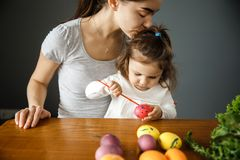 A young woman and her daughter are painting on an easter egg together. stock photo
