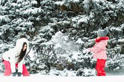 Young woman and her daughter play snowballs in winter forest. Little girl throwing snow stock image