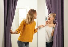 Young woman with her friend in dressing rooms. Young women with her friend in dressing rooms. Fashion store royalty free stock image