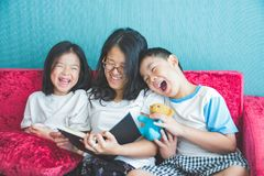 Young woman and her little children reading books on sofa at home. Young women and her little children reading books on sofa at home stock photography