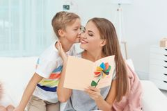 Young woman with her little son and  greeting card. Young women with her little son and  greeting card for Mother`s Day at home Royalty Free Stock Photos