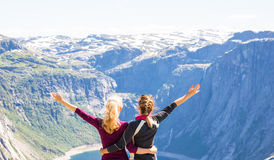 Young women hiking on Trolltunga. Happy friends enjoy beautiful lake and good weather in Norway Stock Photography