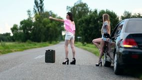 Young women hitchhiking near broken car stock video