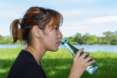 Young women with hold the bottle drinking water Stock Images