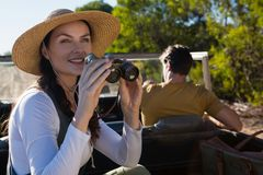 Woman using binocular with man driving off road vehicle at forest Stock Images
