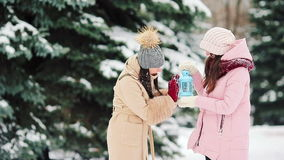 Young women holding candlelight outdoors on beautiful winter snow day and warm their hands stock video footage