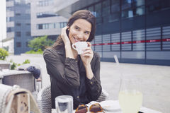 Young women holding coffe cup. Women holding coffe cup and looking at the side Royalty Free Stock Image