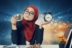 Young women holding coin in glass cup and retro alarm clock over abstract background Stock Photos