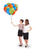 Young women holding colorful balloons Stock Photos