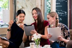 Young women holding files in a coffee shop. Three beautiful young women holding files while sitting in a coffee shop Royalty Free Stock Images