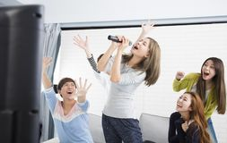 Woman holding microphone and singing at karaoke Royalty Free Stock Photos