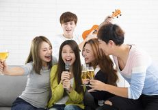 Woman holding microphone and singing at karaoke Stock Photography