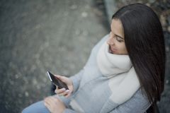 Young Women Holding Mobilephone. Woman sitting on bench and holding cellphone. Close up Stock Photo
