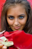 Young women holding petals. Portrait of young women holding petals of the roses on red background. Shallow DOF Stock Photos