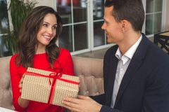 Young couple having romantic dinner in the restaurant holding a present grateful. Young women holding a present looking at men grateful having romantic dinner in Stock Photography