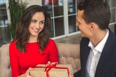Young couple having romantic dinner in the restaurant holding a present. Young women holding a present looking at men having romantic dinner in the restaurant Royalty Free Stock Photo