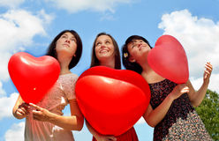 Young women holding red balloons against sky Stock Image