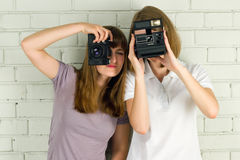 Young women holding vintage cameras Royalty Free Stock Photography