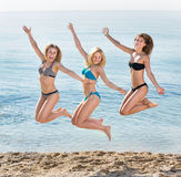 Young women hopping on beach. Portrait of three cheerful young women in swimsuits hopping together on beach. Focus on left person Royalty Free Stock Photography