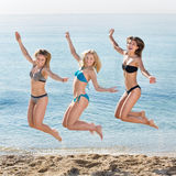 Young women hopping on beach. Portrait of three cheerful young women in swimsuits hopping together on a beach. Focus on right person Royalty Free Stock Photography