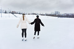 Young women on ice rink rear Royalty Free Stock Photography