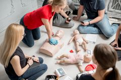 First aid training. Young women instructor showing how to make chest compressions with dummy during the first aid group training indoors stock photos