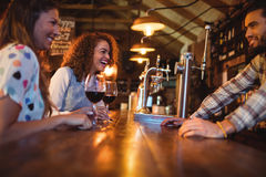 Young women interacting with bartender at counter Stock Images