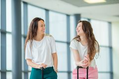 Young women with baggages in international airport. Airline passengers in an airport lounge waiting for flight aircraft. Young women in international airport Royalty Free Stock Photography
