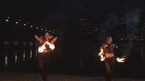 Attractive firegirls juggling lit torches at night stock footage