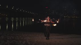 Young women juggling lit torches during fireshow stock footage