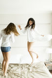 Young women jumping in the bed Stock Photo