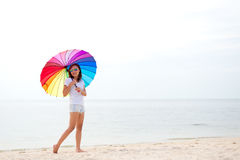 Young women jumping with umbrella and happy on the beach. stock images