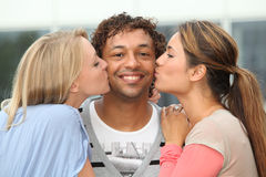 Young women kissing friend. Man receiving kiss from girlfriends Royalty Free Stock Image