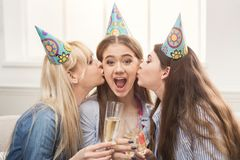 Young women kissing her friend on the cheeks. Celebrating birthday and drinking champagne. Holiday, celebration and female friendship concept, copy space Royalty Free Stock Photography