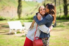 Young woman kissing her friend face outdoors. Young women kissing her friend face outdoors. Blonde and brunette girls wearing casual clothes outdoors Royalty Free Stock Photography