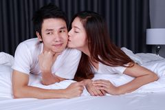 Woman is kissing her husband in cheek on bed Royalty Free Stock Image