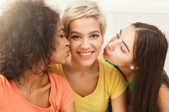 Young women kissing their friend on the cheeks. Friends spending time together, care, friendship, fun concept, copy space Stock Images