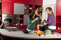 Young women in the kitchen. Pretty young women in the kitchen with glasses of red wine Royalty Free Stock Photography