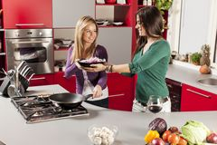 Young women in the kitchen. Pretty young women in the kitchen Royalty Free Stock Image