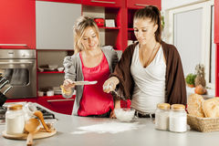 Young women in the kitchen Stock Images